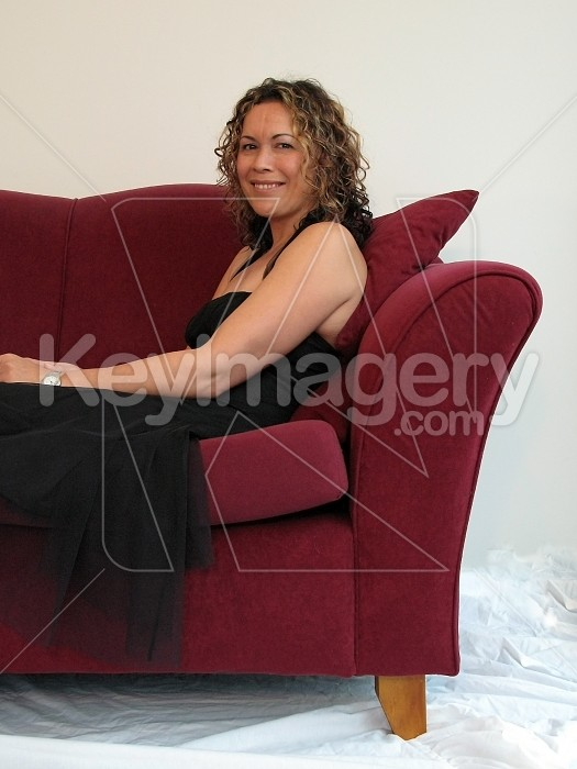 Smiling woman reclining on sofa Photo #4765