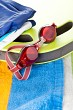 Colourful beach towel and swimming goggles