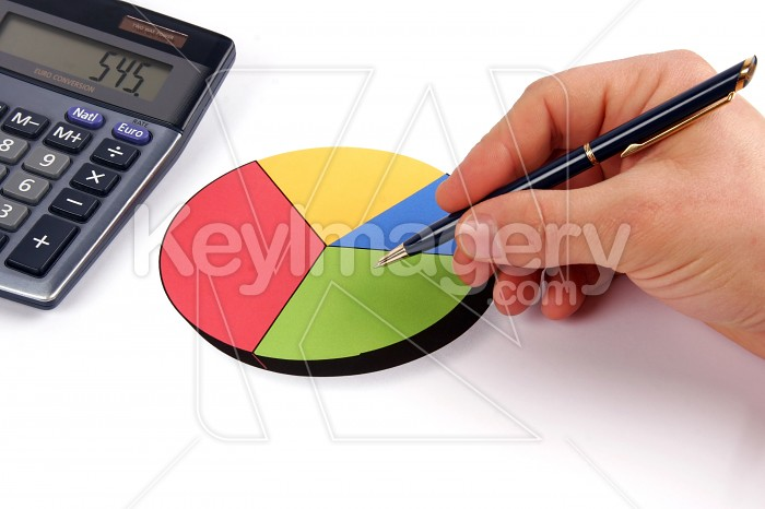 Hand holding a pen showing a diagram on financial report Photo #7816