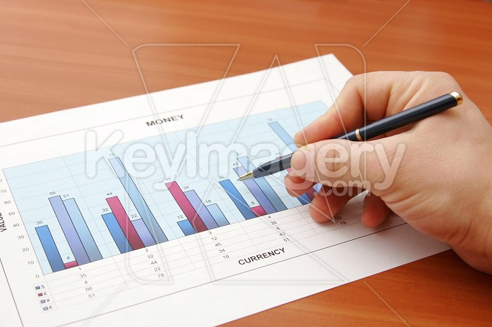 Hand holding a pen showing a diagram on financial report Photo #7819
