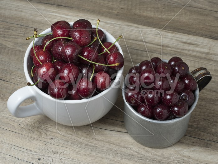 Fresh ripe cherries in cups, on wooden background. Photo #62080
