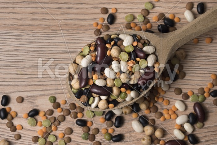 Legumes of various kinds in a wooden spoon on the table. Photo #59381