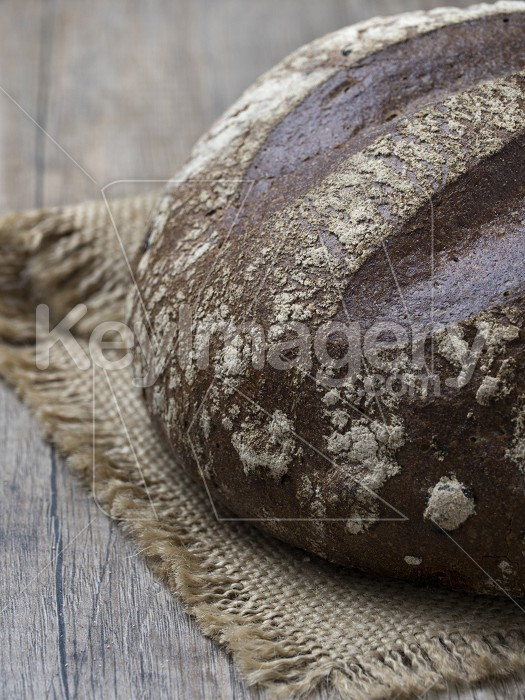 Round loaf of freshly backed sourdough bread on wooden backgroun Photo #59506