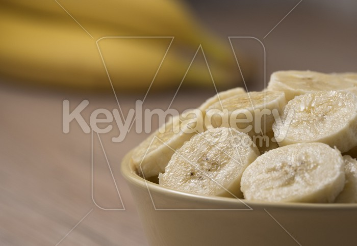 Sliced banana in ceramic bowl on wooden background. Close up. Photo #59392